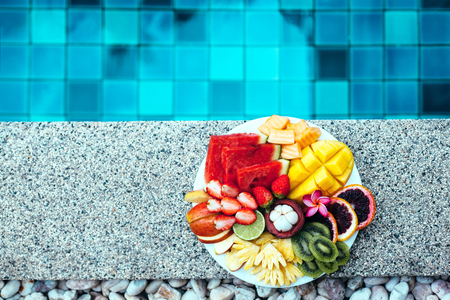 summer diet: Served fruit plate by hotel pool. Exotic summer diet. Tropical beach lifestyle. Stock Photo