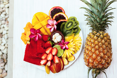 summer diet: Fresh fruit plate and pineapple, top view from above. Exotic summer diet. Tropical beach lifestyle. Stock Photo