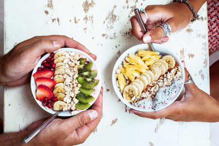 Smoothie bowls with mixed tropical fresh fruits on wooden table with hands, top view from above. Summer healthy diet, vegan breakfast.
