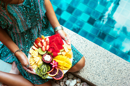 Girl relaxing and eating fruit plate by the hotel pool. Exotic summer diet. Photo of legs with healthy food by the poolside. Tropical beach lifestyle.