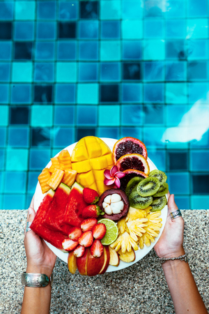 summer diet: Hands holding served fruit plate above hotel pool. Exotic summer diet. Tropical beach lifestyle. Stock Photo