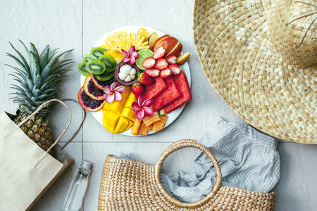 Fresh fruit plate and set of summer fashion beach accessories, top view from above (overhead). Tropical beach lifestyle. Stock Photo