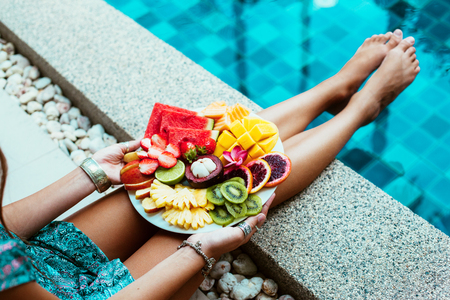 summer diet: Girl relaxing and eating fruit plate by the hotel pool. Exotic summer diet. Photo of legs with healthy food by the poolside. Tropical beach lifestyle.