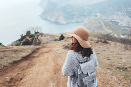Girl wearing hat and sweater travel in mountains alone. Cold weather, calm scene. Backpacker walking outdoors in fall, back view over landscape. Wanderlust photo series. Stock Photo