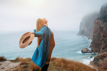 Pregnant girl wearing coat and hat traveling in mountains. Cold weather, calm scene. Happy and healthy maternity. Wanderlust photo series. photo