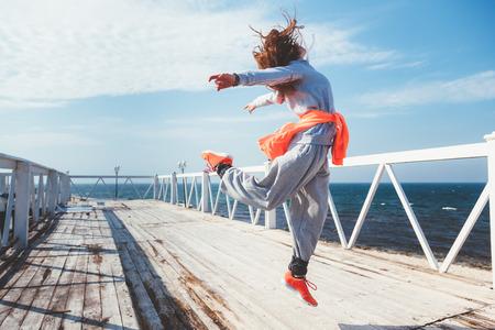 通りでフィットネス運動を行うファッション スポーツウェアでフィットネス スポーツ少女。ヒップホップのダンサー、アウトドア スポーツ。