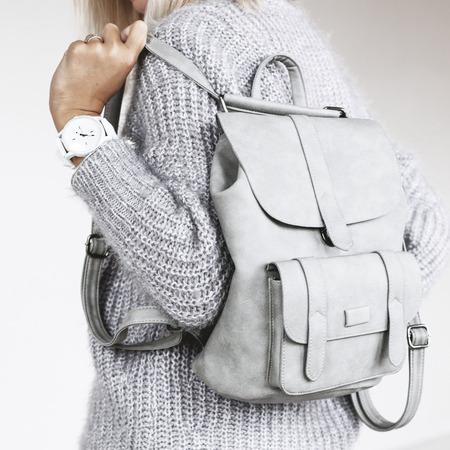 Onherkenbaar model dragen casual outfit en bedrijf lederen rugzak. Grijze kleding in trendy minimalistische stijl. Street fashion voor de lente of herfst. Details van het dagelijkse elegante look. Stockfoto - 74018363