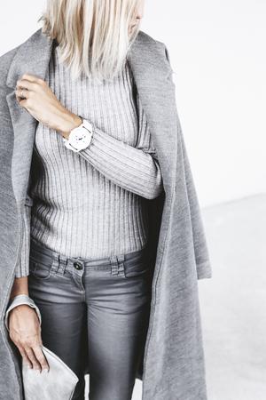 Onherkenbaar model dragen casual outfit en het bedrijf clutch bag. Grijze kleding in trendy minimalistische stijl. Street fashion voor de lente of herfst. Details van het dagelijkse elegante look.
