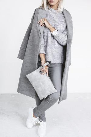 Nicht erkennbare Modell Casual Outfit und Handtasche zu halten. Graue Kleidung im trendigen minimalistischen Stil. Straßenmode für Frühling oder Herbst-Saison. Details des täglichen eleganten Look. Standard-Bild - 73992938