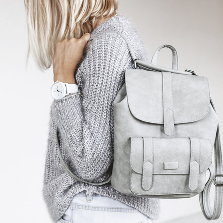 Unrecognizable model wearing casual outfit and holding leather backpack. Gray clothing in trendy minimalistic style. Street fashion for spring or fall season. Details of everyday elegant look.