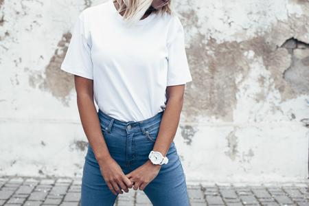 빈 흰색 t- 셔츠와 거친 거리 벽, 미니 멀리 즘 도시 의류 스타일, tshirt 인쇄 저장소에 대 한 mockup에 대 한 포즈 청바지 입고 hipster 소녀
