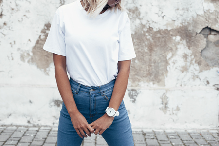 Hipster girl wearing blank white t-shirt and jeans posing against rough street wall, minimalist urban clothing style, mockup for tshirt print store Banque d'images