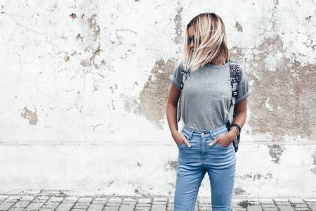 Hipster meisje dragend leeg grijs t-shirt, jeans en rugzak die tegen ruwe straat muur, minimalistische urban kleding stijl, mockup voor t-shirt afdruk store Stockfoto