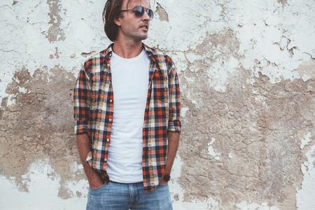 モックアップ モデル、ファッション都市スタイルのフロント t シャツ ストリート壁ポーズ空白の t シャツを着ているハンサムな男