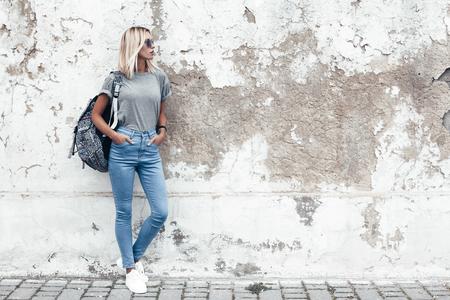 Hipster fille portant un t-shirt gris vierge, un jean et un sac à dos posant contre un mur de rue rugueux, un style de vêtement urbain minimaliste, une maquette pour imprimer des t-shirts