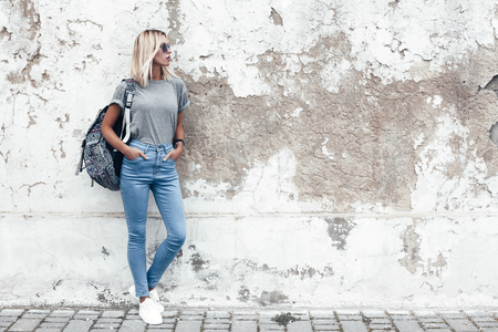 Hipster girl wearing blank gray t-shirt, jeans and backpack posing against rough street wall, minimalist urban clothing style, mockup for tshirt print store Фото со стока - 74995817