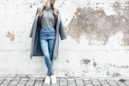 Hipster girl wearing blank gray t-shirt, jeans and coat posing against rough street wall, minimalist urban clothing style, mockup for tshirt print store Foto de archivo