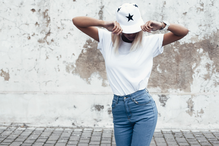 Hipster girl wearing blank white t-shirt, jeans and baseball cap posing against rough street wall, minimalist urban clothing style, mock up for tshirt print store