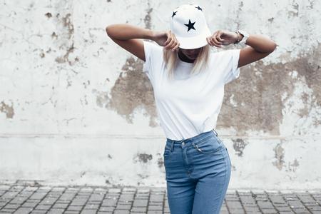 時髦的女孩穿著空白T卹,牛仔褲,棒球帽假扮對粗糙的街道牆壁,簡約的都市服裝風格,小樣的T卹打印店