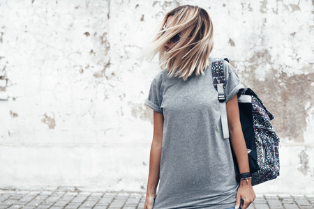 Hipster girl wearing blank gray t-shirt and backpack posing against rough street wall, minimalist urban clothing style, mock up for tshirt print store 免版税图像