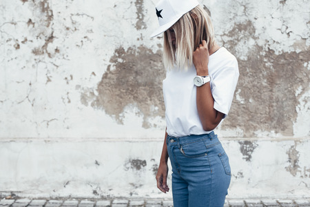 Hipster girl wearing blank white t-shirt, jeans and baseball cap posing against rough street wall, minimalist urban clothing style Imagens