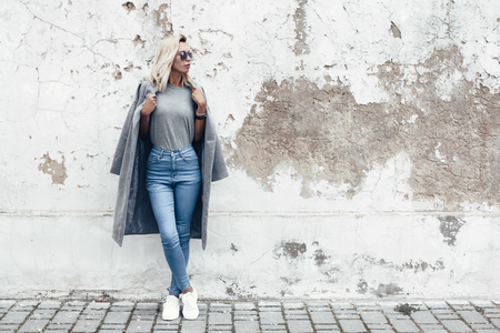 Hipster girl wearing blank gray t-shirt, jeans and coat posing against rough street wall, minimalist urban clothing style, mockup for tshirt print store Stock Photo