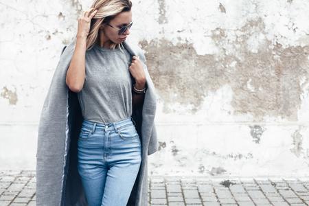 空白のグレーの t シャツ、ジーンズ、大まかなウォールストリート、都市のミニマルな服のスタイル、t シャツ プリント店のモックアップに対するポーズのコートを身に着けている内気な少女