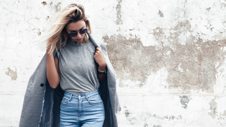 outerwear: Hipster girl wearing blank gray t-shirt, jeans and coat posing against rough street wall, minimalist urban clothing style, mock up for tshirt print store