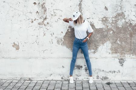 Hipster meisje dat lege witte t-shirt, jeans en baseball cap poseren tegen ruwe straat muur, volledige lengte portret, minimalistische urban kleding stijl, mockup voor t-shirt afdruk store photo