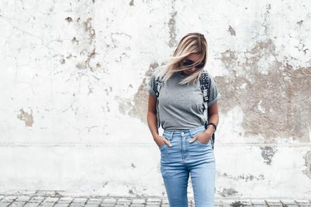 Hipster meisje dragend leeg grijs t-shirt, jeans en rugzak die tegen ruwe straat muur, minimalistische urban kleding stijl, mock-up voor t-shirt afdruk store photo