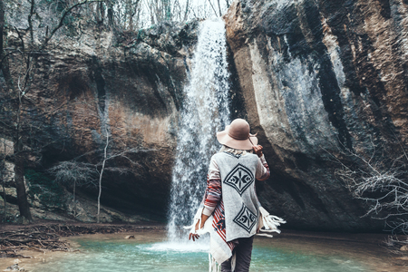 Boho woman wearing hat and poncho standing by the waterfall and looking at it. Cold weather, winter hiking. Wanderlust photo series. Imagens