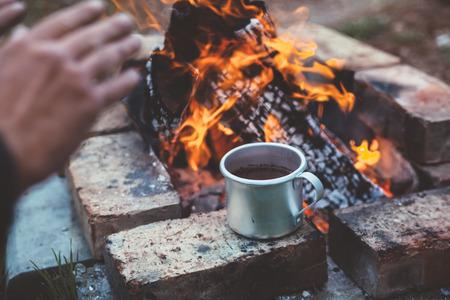 여행자 캠프 야외에서 그의 손을 야외에서 온난 화. 차 또는 배경에 알루미늄 낯 짝에 커피입니다. 캠핑 세부, 여행 라이프 스타일 사진입니다.
