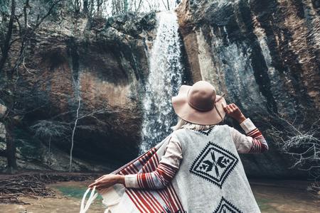Boho vrouw hoed en poncho staan bij de waterval en naar te kijken. Koud weer, herfst wandelen. Wanderlust fotoserie. photo