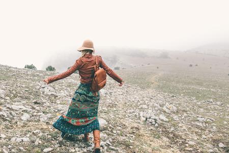 Boho Frau trägt Hut und Lederjacke zu Fuß in den Bergen. Kaltes Wetter und Nebel. Frühlings- oder Herbstwanderung Fernweh. Standard-Bild - 75019948