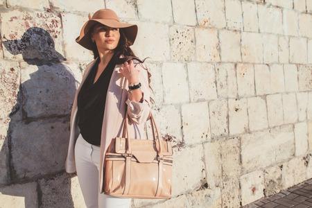 中立的なブレザー、帽子と春の街を歩いてのハンドバッグを着た若いスタイリッシュな女性。カジュアルなファッション、エレガントな外観。プラ