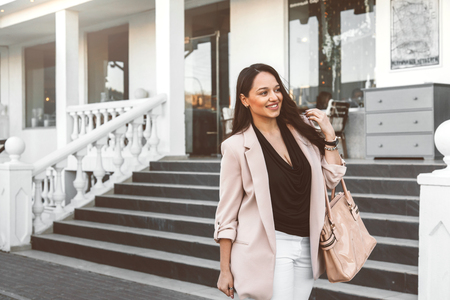 fashion clothing: Young stylish woman wearing neutral blazer with handbag walking on the city street in spring. Casual fashion, elegant look. Plus size model.
