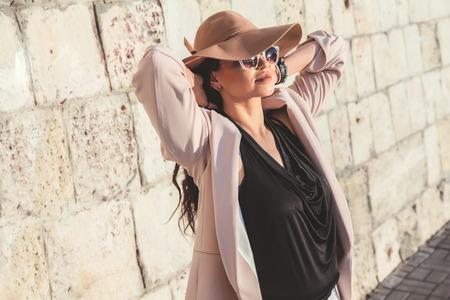 身に着けている中立的なブレザー、帽子とサングラス春の街を歩く若いスタイリッシュな女性。カジュアルなファッション、エレガントな外観。プ