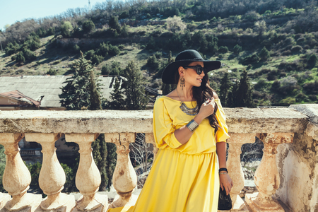 Young stylish woman wearing yellow maxi dress, black hat, sunglasses and handbag walking in the city street. Spring fashion outfit, elegant look. Plus size model.
