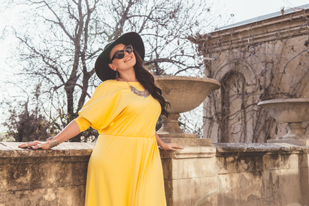 Young stylish woman wearing yellow maxi dress, black hat and sunglasses walking in the city street. Spring fashion outfit, elegant look. Plus size model. Stockfoto
