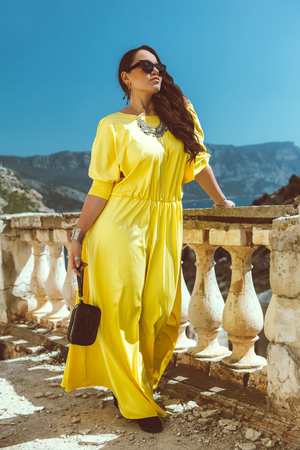 Young stylish woman wearing yellow maxi dress, sunglasses and clutch walking in the city street. Spring fashion outfit, elegant look. Plus size model.