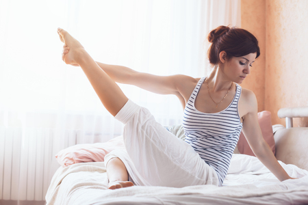 Woman doing yoga exercise on bed at home. Morning workout in bedroom. Healthy and sport lifestyle. Archivio Fotografico