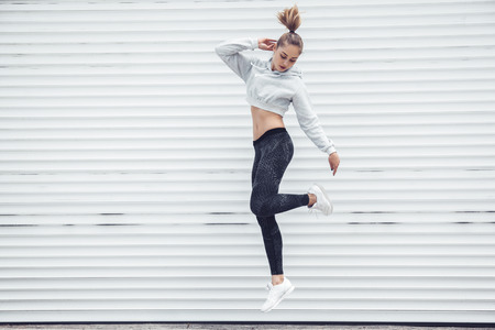 Fitness sporty girl in fashion sportswear dancing hip hop in the street, outdoor sports, urban style. Teen model in swag clothes posing outside. Standard-Bild