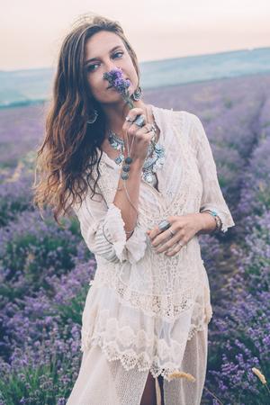 Hermoso modelo de caminar en la primavera o el campo de lavanda de verano en la salida del sol a contraluz. Ropa y joyas de estilo Boho. Foto de archivo