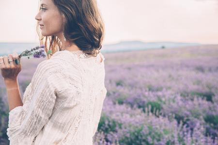 Schöne Modell zu Fuß im Frühjahr oder Sommer Lavendelfeld in Sonnenaufgang Hintergrundbeleuchtung. Boho Stil Kleidung und Schmuck.