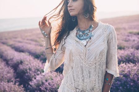 Beau modèle de marche au printemps ou au champ de lavande d'été au lever du soleil rétro-éclairé. Vêtements et bijoux Boho style.