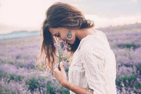 일출 백라이트에서 봄 또는 여름 라벤더 필드를 산책하는 아름 다운 모델. Boho 스타일의 의류 및 보석.