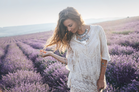 Beautiful model walking in spring or summer lavender field in sunrise backlit. Boho style clothing and jewelry. Zdjęcie Seryjne - 81516335