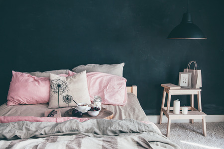 Black and pink stylish loft bedroom. Unmade bed with breakfast and reading on tray. Lamp and interior decor over blank blackboard wall with copyspace. Cozy modern living space.