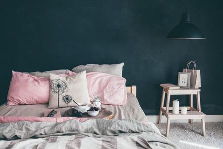 Dormitorio estilo loft negro y rosa. Cama sin desayunar con desayuno y lectura en la bandeja. Decoración de la lámpara y del interior sobre la pared en blanco de la pizarra con el copyspace. Acogedor espacio de vida moderna. Foto de archivo - 81879739