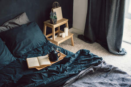 Black stylish loft bedroom. Unmade bed with breakfast and reading on tray. Cozy modern living space. Stockfoto